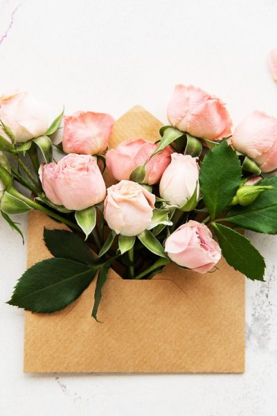 Envelope and pink roses on a white marble background